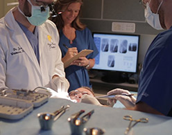 small photo of staff performing dental procedure